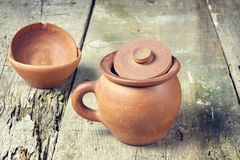 Clay pot with with clay cup. On old grunge table Stock Images