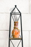 Clay pot coral home house decor elements arrangement on metal stand against the wall Stock Photo