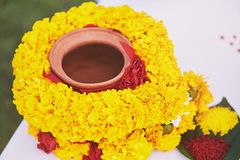 Indian wedding prayer items for thread ceremony, pooja Puja, focused on center of clay pot. The clay pot cover with yellow garland, The prayer and worship items Royalty Free Stock Image