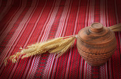 Clay pot covered with a lid and wheat sheaf Royalty Free Stock Photos