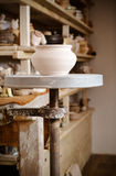 Clay pot in the foreground and shelves with pottery - on the second Royalty Free Stock Image