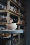 Clay pot in the foreground and shelves with pottery - on the second Royalty Free Stock Photo