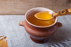 Clay pot with ghee and spoon on linen napkin. Rustic still life. Wooden background Stock Images