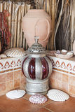 Clay pot and lantern. Stones and seashells in the Desert Camp royalty free stock photography