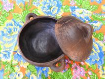 "Clay pot with lid, handicraft of Brazilian indigenous origin, on a very colorful ""chitao"" fabric. stock photos"