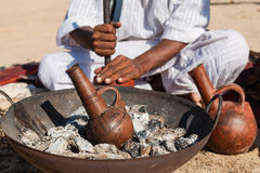 Clay pot. Marsa Alam, Red Sea/ Egypt – OCTOBER 31: Coffee clay pot called fakhara in foreground while unidentified Bedouin young man from Bishari Tribe grind Royalty Free Stock Photo