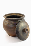 Clay pot open. Dark open clay pot with cover over white background Royalty Free Stock Images