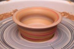 Clay pot on a potter wheel Stock Photos