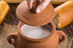 Clay pot with rustic milk and hot baguette Royalty Free Stock Image
