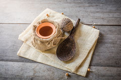 Clay pot in sack bag and wooden spoon Royalty Free Stock Image