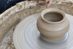 Making a pot of clay. The clay pot is spinning and made. Ceramics stock photo