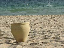 Clay pot stands on the sand by the sea, Africa royalty free stock photo