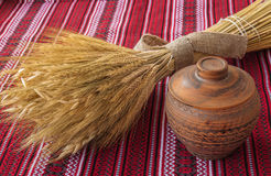 Clay pot and wheat sheaf on the Ukrainian homespun fabric Royalty Free Stock Image