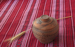 Clay pot and wheat sheaf on the Ukrainian homespun fabric Royalty Free Stock Images