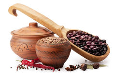Clay pot, wooden spoon, lentils, beans and spices royalty free stock photography