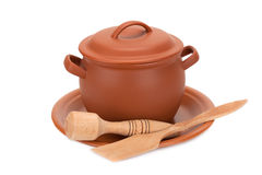 Clay pot, wooden utensils on a plate Stock Photos