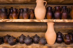 Clay pots. Abundance of clay pots on the top and lower shelf stand in a row Royalty Free Stock Image