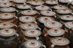 Clay pots with covers. A view of a rows of identical clay pots with matching covers Stock Image