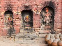 Clay pots drying next to three niches with old carved hindu deities. Clay pots drying next to three different-sized niches with old carved hindu deities covered royalty free stock photo
