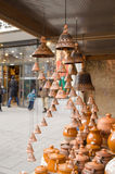 Clay pots hang bells ware store shop market people. Clay pots and hanging bells wares sold in outside store shop market and people walk in city street stock photography