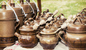 Clay pots with honey dippers Royalty Free Stock Photos