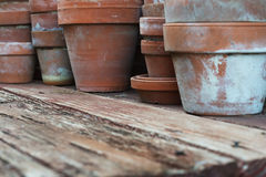 Clay pots on rough wood. Closeup of used clay flowerpots on a rough wooded tabletop stock images