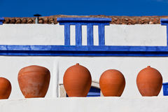 Clay pots stand on white pottery wall in Portugal Royalty Free Stock Photography