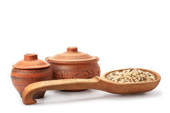 Clay pots, wooden spoon and rice Royalty Free Stock Photography