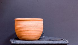Clay Pottery againts grey. Clay pot standing on antique stove against nice smooth grey background Stock Photo
