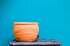 Clay Pottery againts terquoise. Clay pot standing on antique stove against nice smooth terquoise background Stock Image