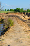 Clay road on the top of the water barrier. With plants Stock Photography
