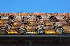 Clay roof tiles of traditional building. Traditional roof tile with tiles and cement and plaster of historic urban or rural building Stock Image