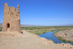 Clay ruin with date palm oassis and river. Clay ruin with date palm oassis, river and a cloudless blue sky Stock Image