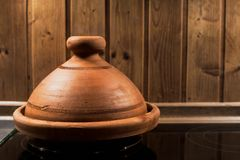 Clay tagine on stove with wooden background - copy space stock image