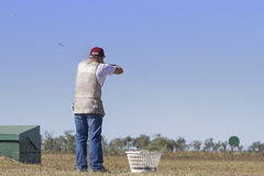 Clay Target Shooting. Clay target shooter aiming at the clay target, showing wad and shot chasing the clay Royalty Free Stock Photo