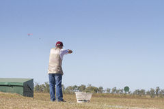 Clay Target Shooting. Clay target shooter aiming at the clay target, showing wad and shot hitting the clay Stock Photos