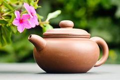 Clay tea pot. A brown clay tea pot on a table outside next to some flowers Royalty Free Stock Photography