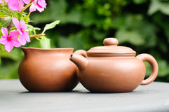 Clay tea pots. A brown clay tea pot on a table outside next to some flowers royalty free stock photos