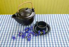 Clay tea set with fresh picked cornflower on table Royalty Free Stock Photos