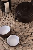 Clay tea set and natural fibers. Clay tea pot and cutp with a mat and support in natural fibers royalty free stock photos