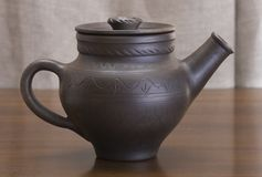 Clay teapot. The clay  teapot on a wooden table Royalty Free Stock Image
