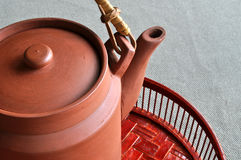 Clay teapot on bamboo basin. A clay teapot rest on a pained bamboo basin Stock Images