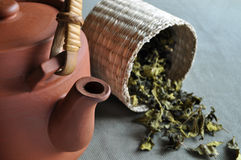 Clay teapot and basket of tea. A clay teapot with a bsket of dried tea leaves as background Royalty Free Stock Images