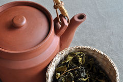 Clay teapot and basket of tea leaves Royalty Free Stock Images
