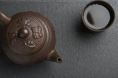 Clay teapot with clay cup full of green tea on black slate background. Traditional clay teapot with clay cup full of green tea on black slate background Stock Photography