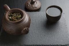 Clay teapot with clay cup full of green tea on black slate background. Traditional clay teapot with clay cup full of green tea on black slate background Royalty Free Stock Photos