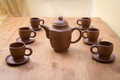 Clay teapot and cups on a table Royalty Free Stock Photography
