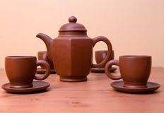 Clay teapot and cups on a table Stock Images