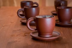Clay teapot and cups on table stock images