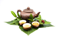 Clay teapot and cups with tea leaves Stock Photography